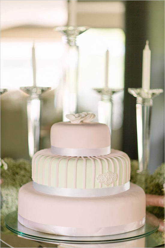 The details here are slight — ribbon, lines on the middle tier, and two top flowers — making this cake effortlessly unique.  Photo by Branco Prata via Wedding Chicks