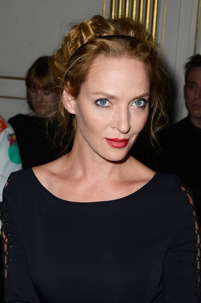 Front row at Versace, Uma Thurman paired a crimson lip with simple black eyeliner. Her hair was pulled back, curly, and kept in place with a classic black headband.