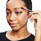 Cover the glue with translucent powder and add foundation using a fluffy brush.