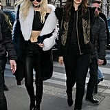 Kendall and Gigi showed off their new hair colors after the Balmain runway show, Gigi wearing a fur-finished Etro vest, Sandro booties, and round sunglasses.