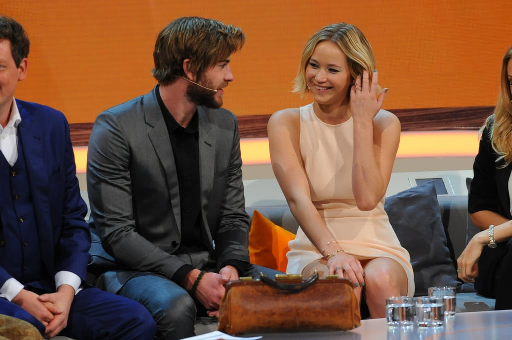 Jennifer Lawrence kicked off the promotional tour for Mockingjay: Part 1 in Germany on Saturday when she joined costar Liam Hemsworth on the German talk show Wetten, dass . . ? Josh Hutcherson was meant to join Jennifer and shaggy-haired Liam on the show but was apparently too sick to attend the taping. However, Jennifer did note that she was battling the same illness — strep throat — which led to some jokes about kissing costars. The trio will have to soldier on through their illnesses as they continue with their press tour leading up to the Nov. 21 release of the highly anticipated film. Aside from battling a sickness, Jennifer has also been facing rumors about the status of her relationship with Chris Martin. There have been conflicting reports about whether the pair are still dating after the two allegedly split up in late October. Either way, the next few weeks will likely be very busy for Jennifer, and she will be tied up in promotional duties and a worldwide tour.