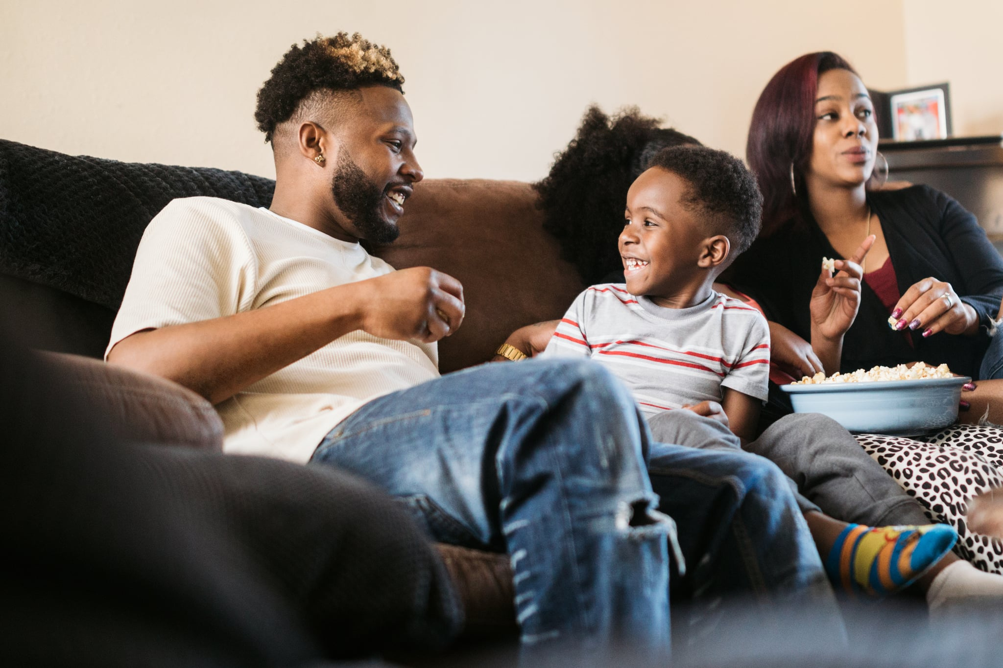 A fun African American family gets cosy on the sofa with a bowl of popcorn for their weekly movie tradition.  A time of connection and tenderness.