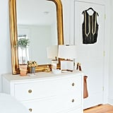 A large, gilded mirror is one of the focal points in the bedroom.