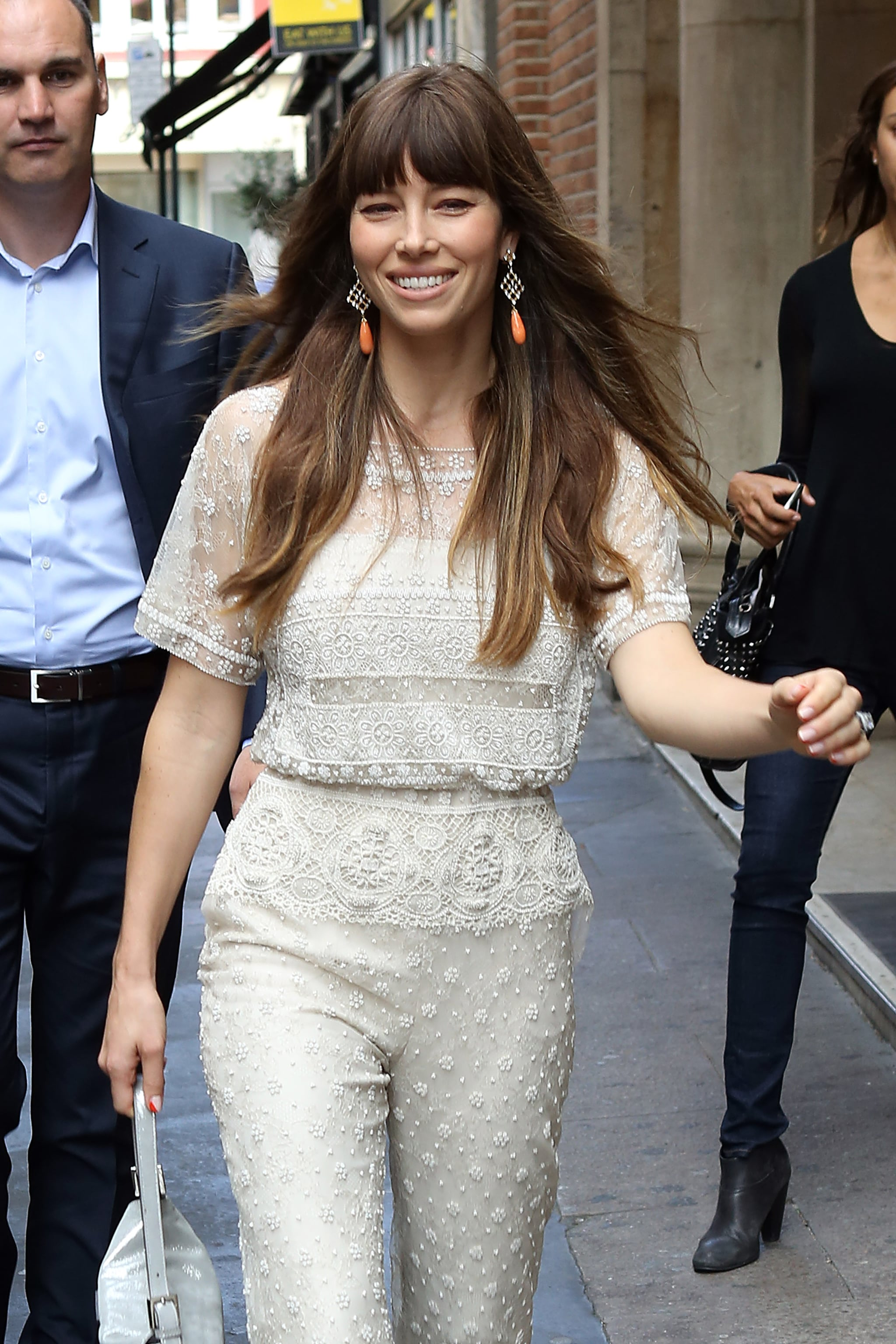 Jessica Biel wore orange earrings with an ivory jumpsuit in London.