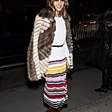 Arriving at the Carolina Herrera show, Olivia layered a fur coat over her white sweater and printed skirt by the Carolina Herrera. She completed the look with a black belt at the waist and Christian Louboutin knee-high boots.