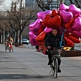 A vendor rides his bicycle laden with heart-shaped balloons down a street in Beijing.