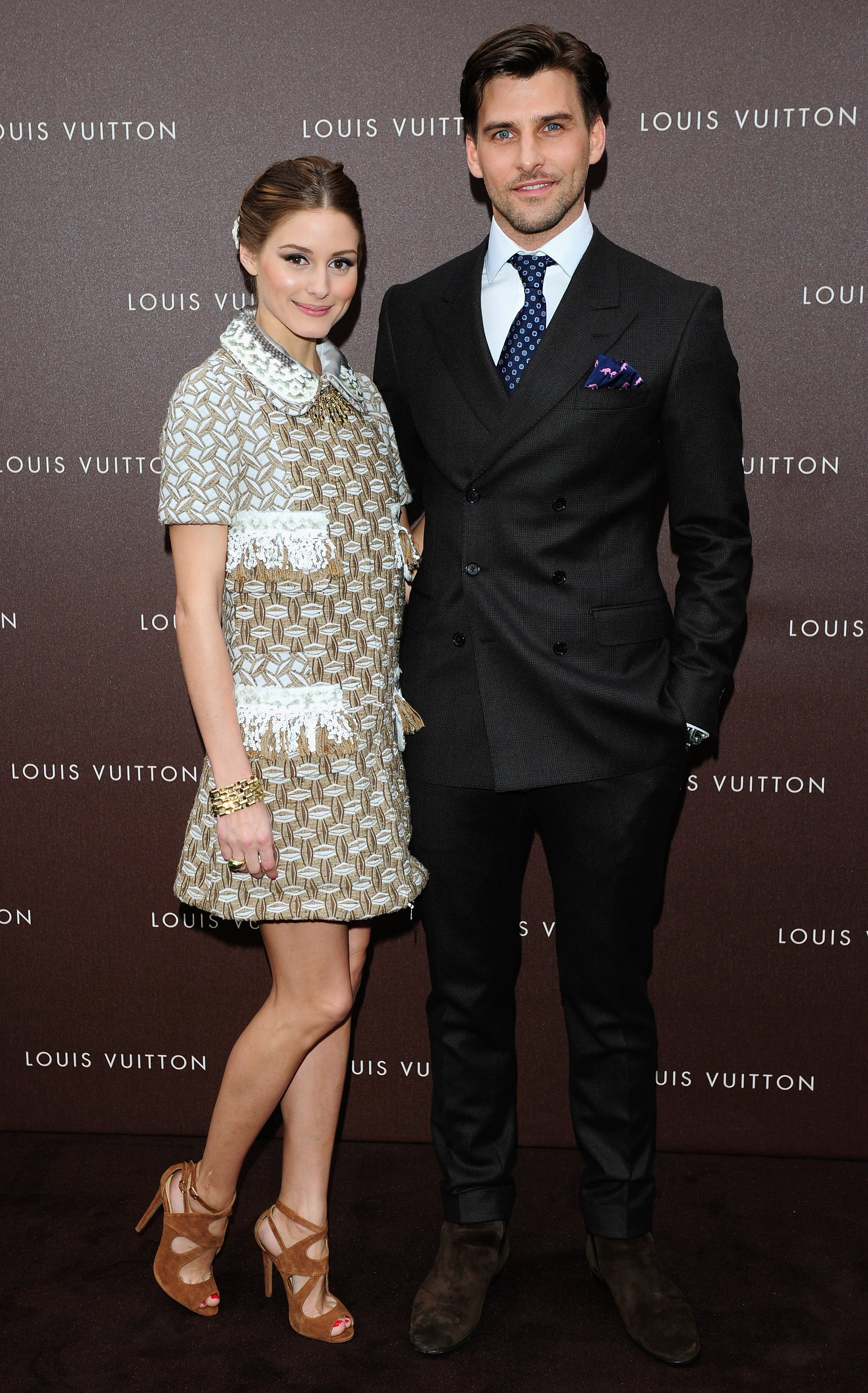 At the Louis Vuitton Maison opening in Munich, Olivia Palermo — pictured with fiancé Johannes Huebl — mixed high with low in a metallic collared Louis Vuitton Resort '13 dress and tan suede Zara sandals.