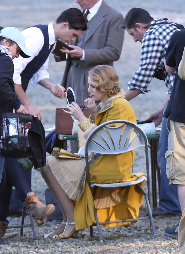 Blake Lively looked like she stepped right out of the roaring '20s when she wore a yellow ensemble on the set of her new film, The Age of Adaline, in Burnaby, Canada, on Wednesday. The actress smiled and giggled with her costars while shooting a scene on the shore and was later seen doing her own makeup touchups during a bit of downtime. Blake has been working hard on the new project for the past two months, and she has been getting frequent on-set visits from her husband, Ryan Reynolds. Last week, Blake had a bit of a scare when she cut herself during filming, but it looked like she was back in the swing of things this week.