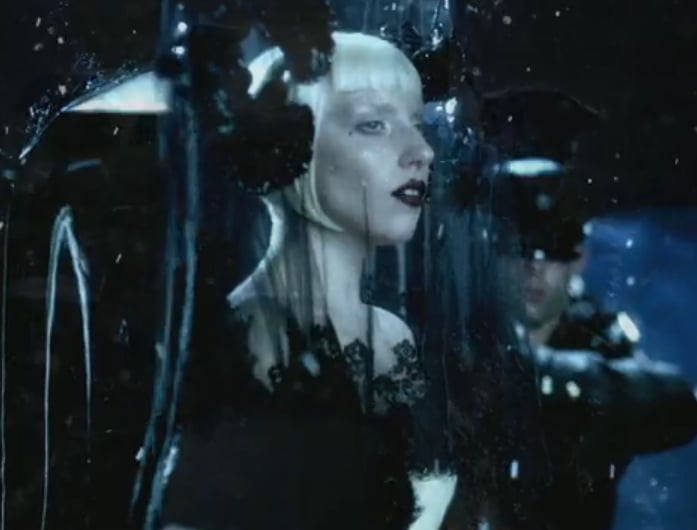 Only Gaga can make a funeral scene chic. The singer covers herself with a delicate black veil with rosette details.