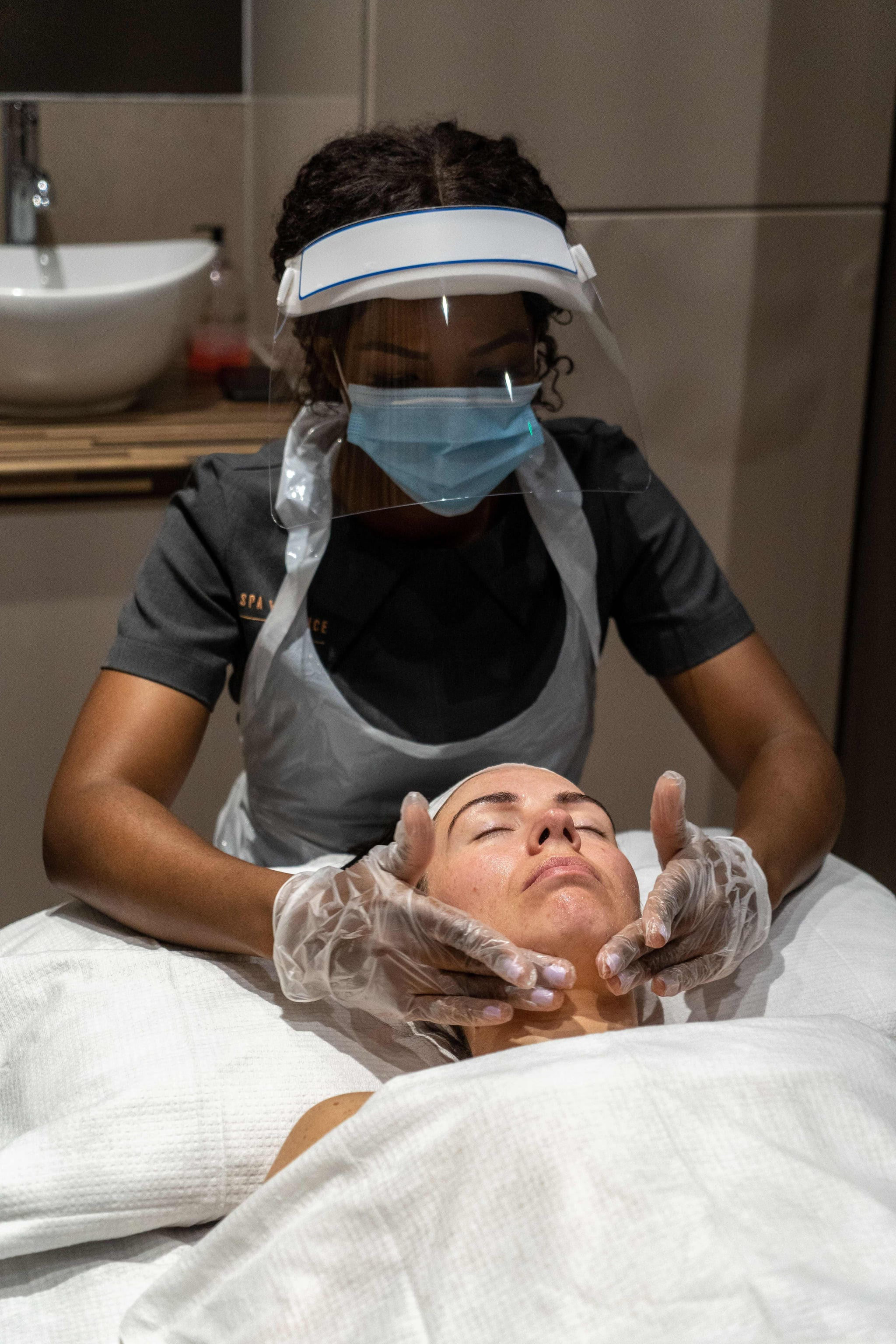 Wearing full PPE (personal protective equipment), Theresa Shangazhike, manager of the Spa Experience Wimbledon, gives her client, Lauren Shine a facial treatment in Wimbledon, south London on August 15, 2020, as beauty salons, spas and hairdressers relax the regulations to combat the coronavirus, now offering additional services, including front-of-face treatments. (Photo by Niklas HALLE'N / AFP) (Photo by NIKLAS HALLE'N/AFP via Getty Images)