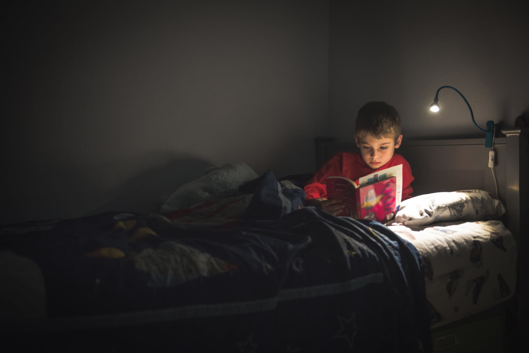 An 8 year old boy is in his bed at night.  His room is dark and lit only by his reading lamp illuminating him and his book.