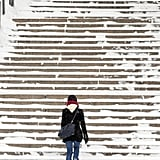 In Boston, MA, a woman made her way up the snowy City Hall steps.