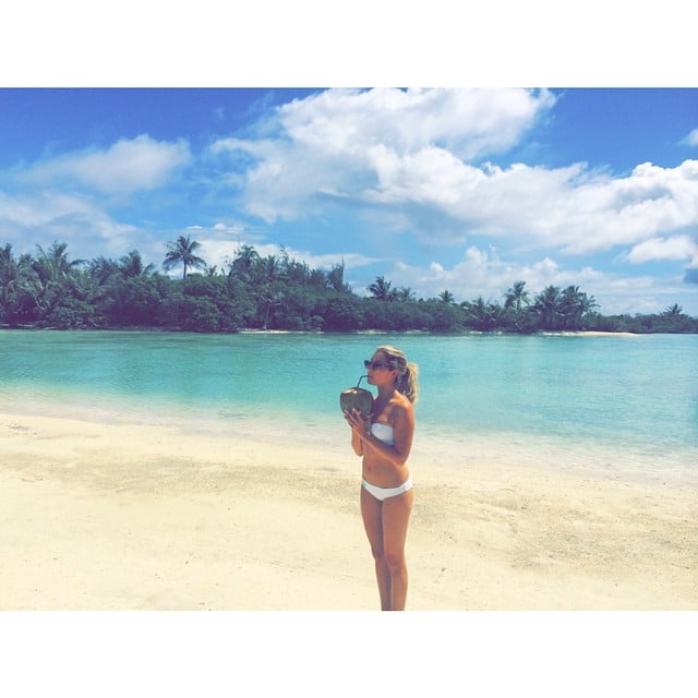 Ashley sipped out of a coconut on the beach during her honeymoon.