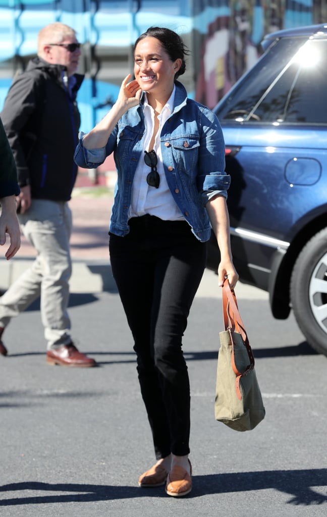 Meghan, Duchess of Sussex Wears Black Jeans with A White Blouse, and Denim Jacket
