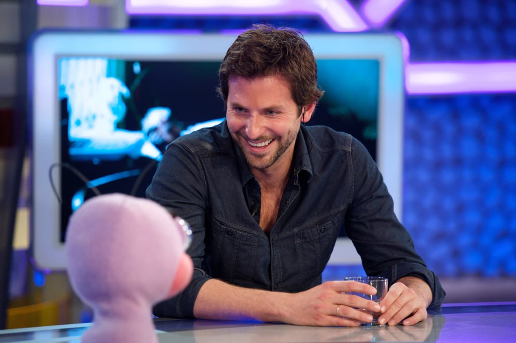 Bradley Cooper is the latest celebrity to join in the fun on Spain's El Hormiguero TV program yesterday. Orlando Bloom was recently coaxed into wearing a blond wig, and Jennifer Aniston planted a kiss on the famous purple ant puppet during her visit. It seems Bradley was willing to blow up balloons and play games while chatting up his latest blockbuster, Limitless. The film was box office champion for its opening weekend in the States, and now he's in the midst of promoting the thriller overseas. Meanwhile, Bradley inadvertently pulled an early April Fools' joke last week when he teased that The Hangover Part II trailer was going to drop today, but it actually was released last night — check out the wild and crazy preview on Buzz!