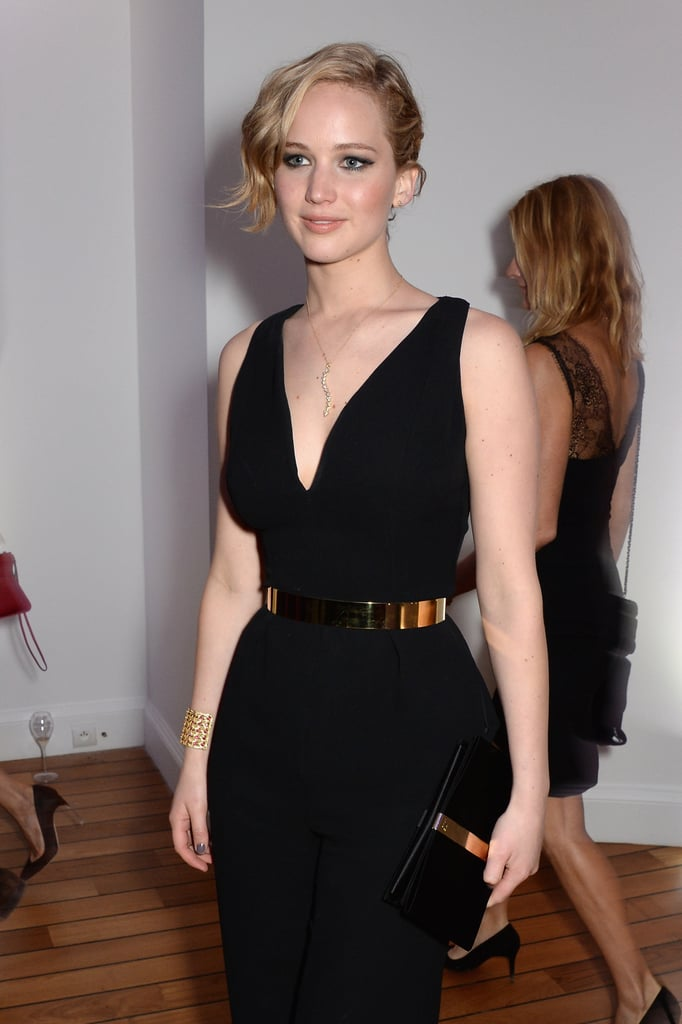 Jennifer Lawrence wore a black dress with gold accessories.