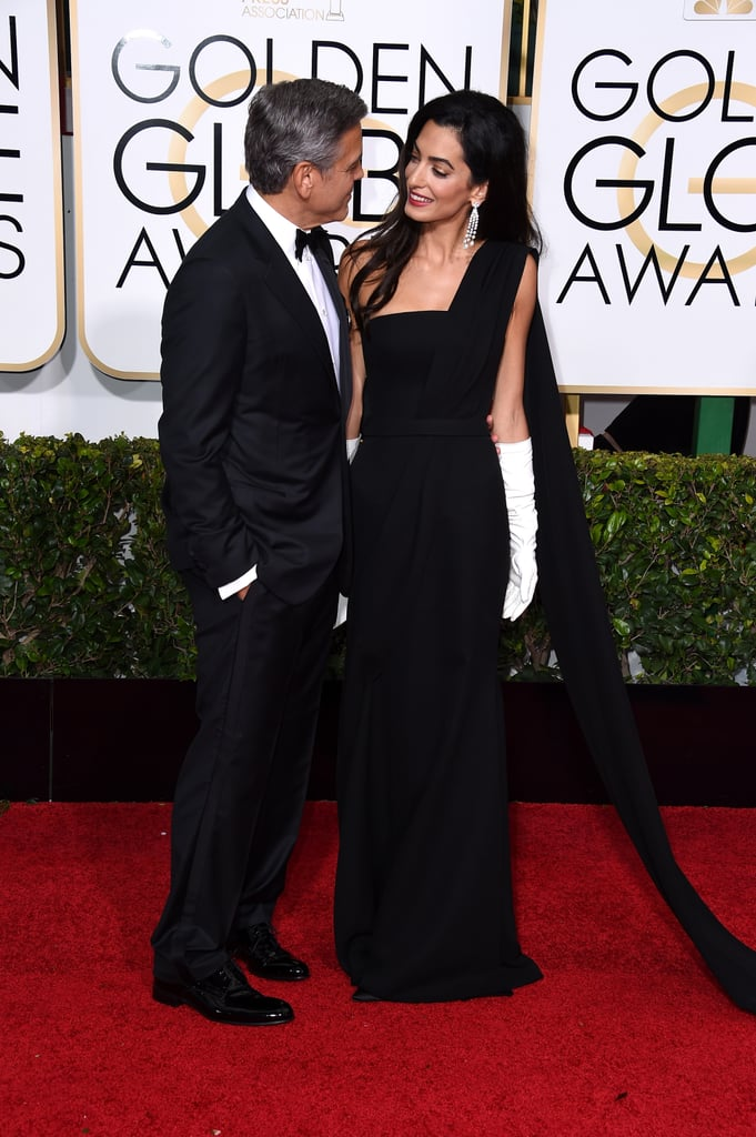 "George Clooney arrived in style for the Golden Globe Awards in LA on Sunday. The actor was joined by his stunning wife, Amal Alamuddin, who made her first-ever award season appearance in a gorgeous black Dior Haute Couture gown  with her own opera-length white gloves. The couple was all smiles while posing for photos together, and during an interview, George revealed that he was doing whatever he could to keep Amal's dress train ""from getting stepped on."" George will be hitting the stage tonight to accept the Cecil B. DeMille Award in celebration of his work both in front of and behind the camera; he'll be honored with the trophy by none other this his former ER costar Julianna Margulies, whom he has remained close friends with since he left the medical drama in 1998. George and Amal's red carpet debut comes after the couple rang in the New Year in Mexico with their good friends Rande Gerber and Cindy Crawford, who were also on hand with them at the Globes. It was likely a relaxing end to a busy year for the pair, who made headlines with their lavish Italian wedding in September, shortly before Amal earned the top spot in Barbara Walters's 10 most fascinating people of 2014. Keep reading for more photos of Amal's first time at the Golden Globes, plus all the pics of George's big night."