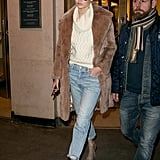 Wearing a pair of Frame Denim boyfriend jeans with a sweater, furry coat, and lace-up heels.