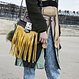 She added even more drama to a Prada face coat with her high-impact fringed bag.