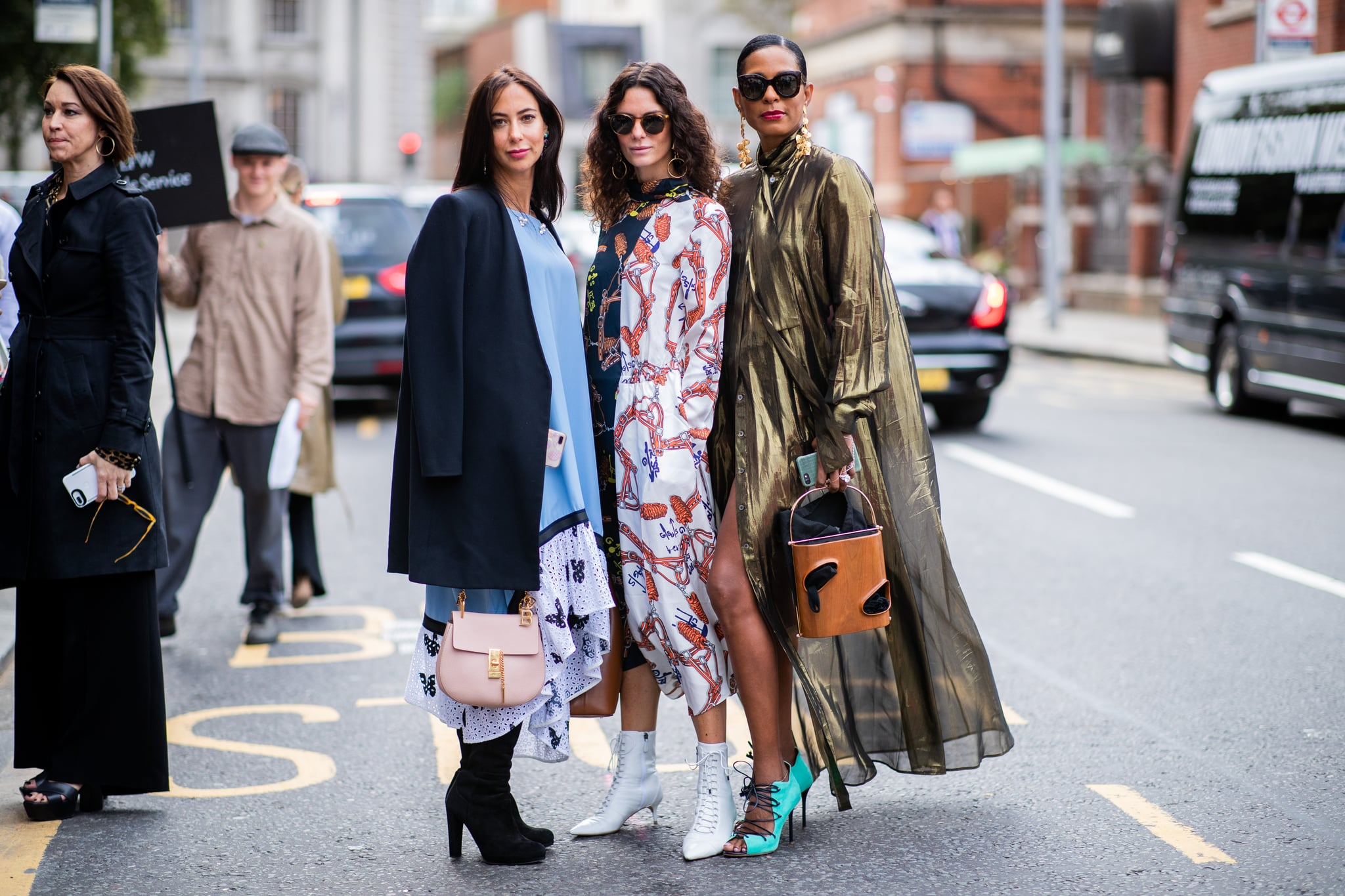LONDON, ENGLAND - SEPTEMBER 18: A guest  wearing pink Chloe bag, blue dress, Hedvig Sagfjord Opshaug wearing two tone dress with print, brown leather bag, white ankle boots and a guest wearing golden coat is seen outside Natasha Zinko during London Fashion Week September 2018 on September 18, 2018 in London, England. (Photo by Christian Vierig/Getty Images)