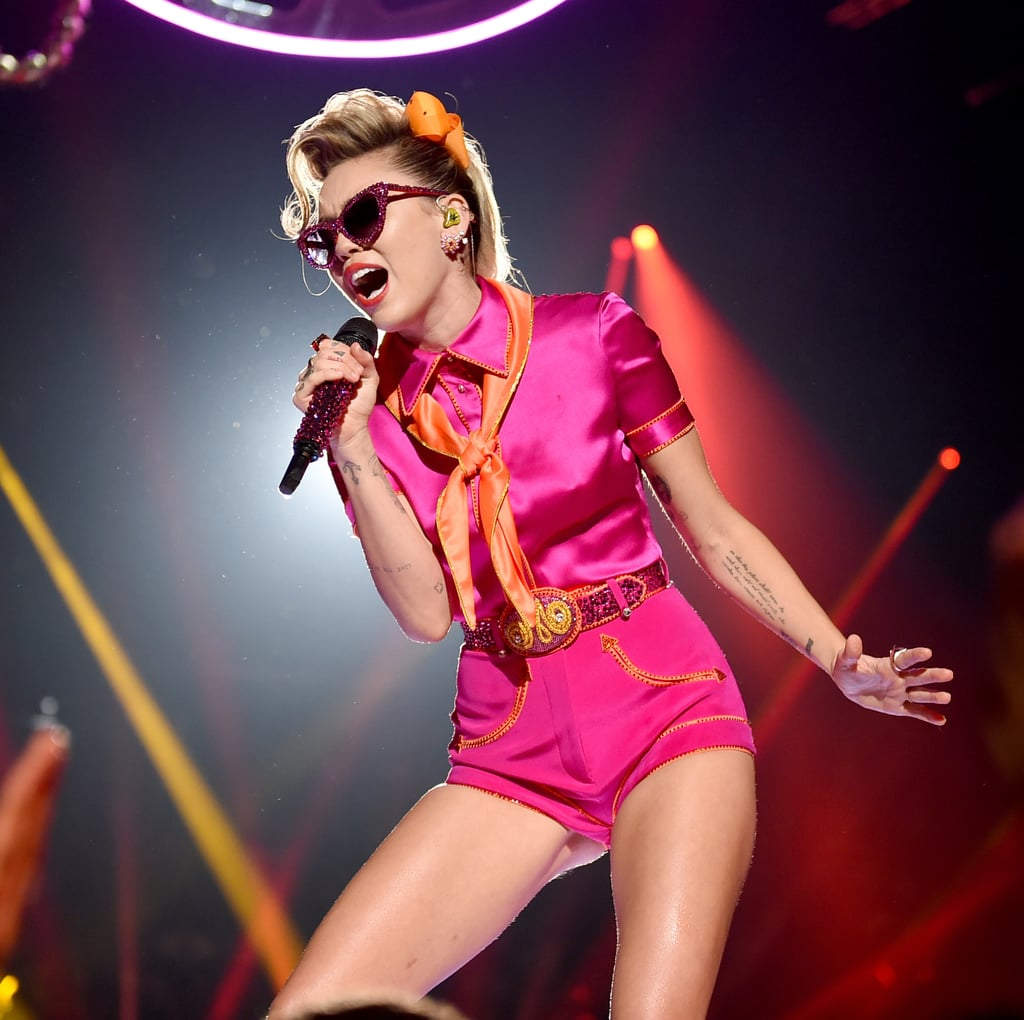 "Miley Cyrus took it back to the '50s for her 2017 MTV VMAs performance, and man are we here for it! While she belted out her new single, ""Younger Now,"" we couldn't help but admire Miley's rockabilly outfit. At first, she was sporting a bright pink playsuit by August Getty Atelier, which she paired with an orange neck scarf, pink heels, and bedazzled cat-eye sunglasses. Then, at the blink of an eye, she switched up her ensemble by throwing on an orange poodle skirt . . . but instead of featuring a poodle like the skirts typically did back in the '50s, Miley's had her initials monogrammed on it. So cute! Scope out Miley's performance outfit from every angle in the photos below."