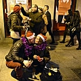 A curbed couple donning Santa hats got kissy in Madrid, Spain.