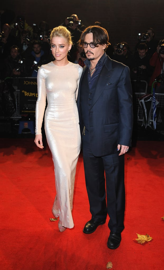 In November 2011 at The Rum Diary premiere in London, Amber posed with her costar Johnny Depp in a shiny, formfitting long-sleeved gown that revealed all her curves.