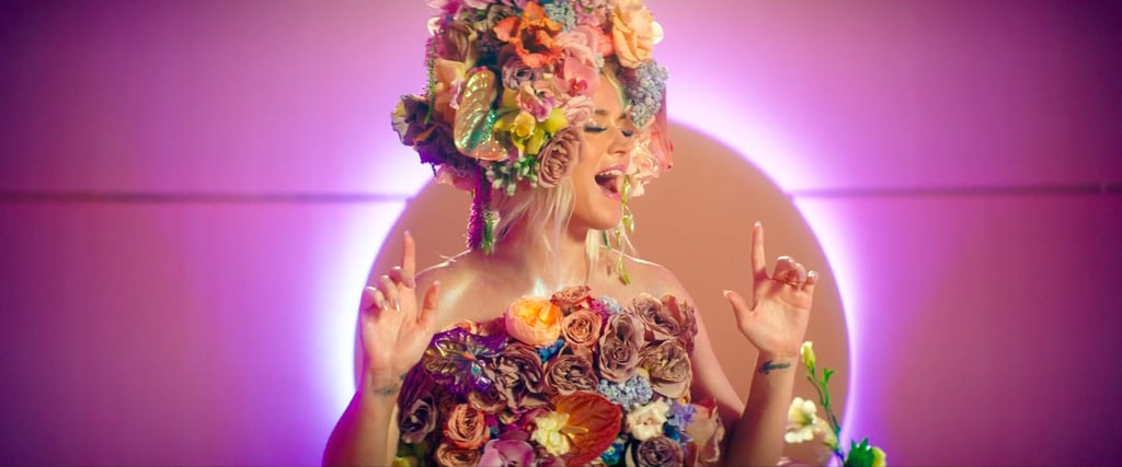 """Katy Perry's latest music video confirmed two things: she's pregnant, and she's seen Midsommar. In the ethereal video for """"Never Worn White,"""" an apparent ode to her fiancé, Orlando Bloom, the singer wears an explosion of colorful flowers not unlike the ceremonial garb Dani Ardor (Florence Pugh) wears after — spoiler alert! — being crowned the May Queen. The head-to-toe equivalent of a flower crown was created by botanical artist Kristen Alpaugh of FLWR PSTL. In addition to the cascading dress resembling a small mountain, Kristen also fashioned a bulbous headpiece for Katy to wear in the video as well as the single's cover art. For a more demure look, Katy also wore a white Alexis Mabille dress featuring an off-the-shoulder neckline almost resembling wings. It's in this dress that Katy acknowledges her pregnancy by cradling her baby bump.  Watch the news-making music video ahead before taking a closer look at what we're dubbing her Midsommar maternity style.      Related:                                                                                                           """"Bouquet Dressing"""" Is the Spring 2020 Trend of Mixing Florals, and You'll See It Everywhere"""