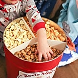 Snack on gourmet popcorn from gigantic holiday-decorated tins.
