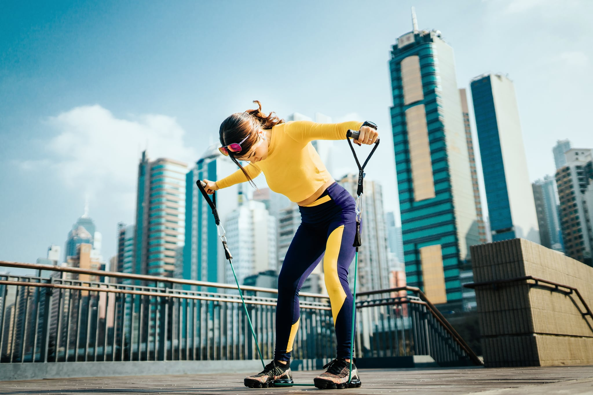Young Asian sports woman exercising with a resistance band outdoors, with urban city skyline as background