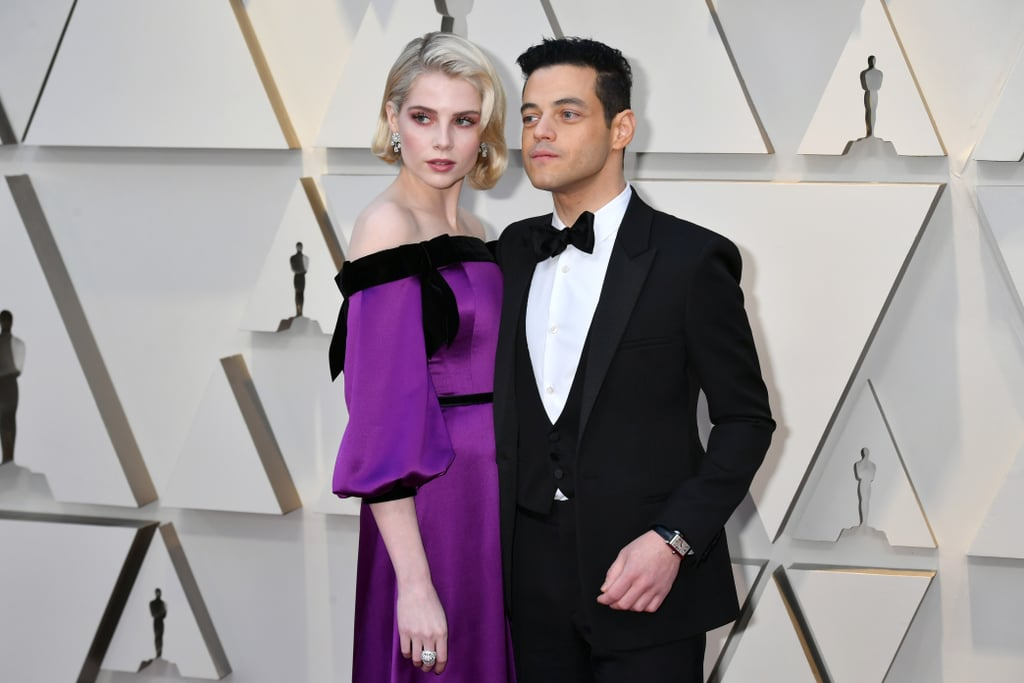 Rami Malek and Lucy Boynton certainly looked aristocratic as they walked the Oscars red carpet covered in Cartier jewels. While the Bohemian Rhapsody co-stars have been quiet about their off-screen romance, they are no strangers to fashion. Malek and Boynton weren't afraid to show off their classic Hollywood style — particularly Boynton, who was a true killer queen in a plum off-the-shoulder gown with black velvet bow accents. Boynton accessorized the satin dress with Marilyn Monroe glamour waves, paired with a Cartier jewel ring and earrings that left her looking ready for a night at the opera.  Malek kept it classic in a custom three-piece black tuxedo from Saint Laurent by Anthony Vaccarello, accessorized with a Cartier watch and matching cufflinks. Even though he needed some help from Lady Gaga to fix his crooked tie, Malek truly captured the vintage Hollywood style as he accepted his Oscar for lead actor.