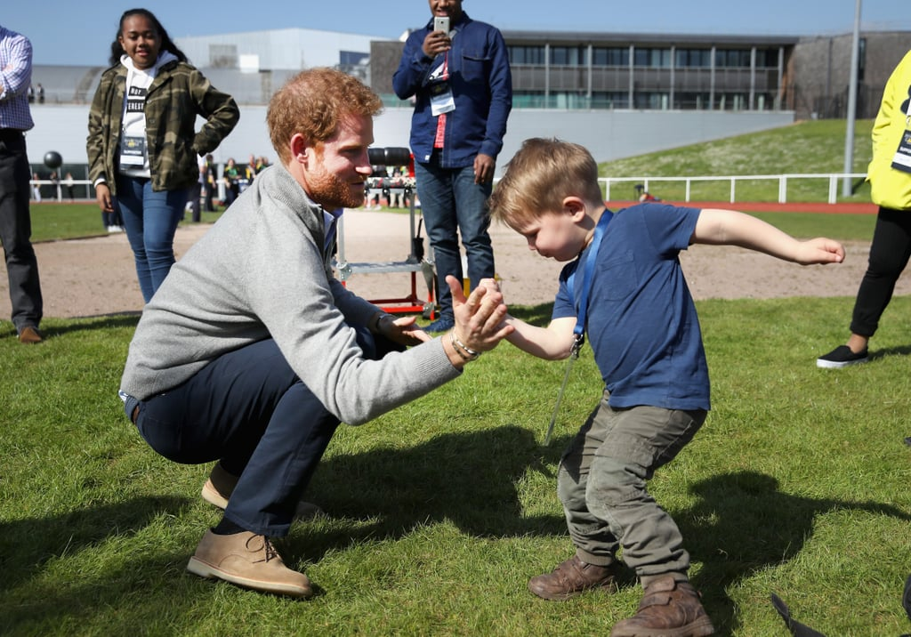 Whenever Prince Harry is around little kids, he basically turns into a giant teddy bear, which is exactly what happened when the 32-year-old royal attended the UK team trials for the Invictus Games on Friday. In between supporting the event's incredible athletes at the University of Bath, Harry looked absolutely delighted while chatting and high-fiving 2-year-old Harry Phillips. Later on he shared a conversation with competitor Jon Flint and his dog, Jester, who Harry couldn't resist giving a few cuddles.  Harry, a patron of the Invictus Games, has been extremely involved ever since coming up with the idea for the competition after seeing the Warrior Games in Colorado. Last year he kicked off the Invictus Games in Orlando, FL, with the help of Michelle Obama, bringing tons of special attention to the event, which is the only international sport competition for wounded, injured, and sick servicemen and women. Harry has had a number of incredibly meaningful interactions with the athletes since its inception, and his dedication will hopefully keep the Invictus Games alive for years to come.