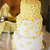 What better way to leave a lasting impression than with bright cascading daisies on a cake? Photo by Austin Gros via Wedding Chicks
