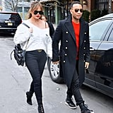 Chrissy walked hand in hand with John Legend wearing an off-the-shoulder white sweater, skinny jeans, and a Gucci belt. She finished off her look with a Chanel backpack and Yeezy boots.