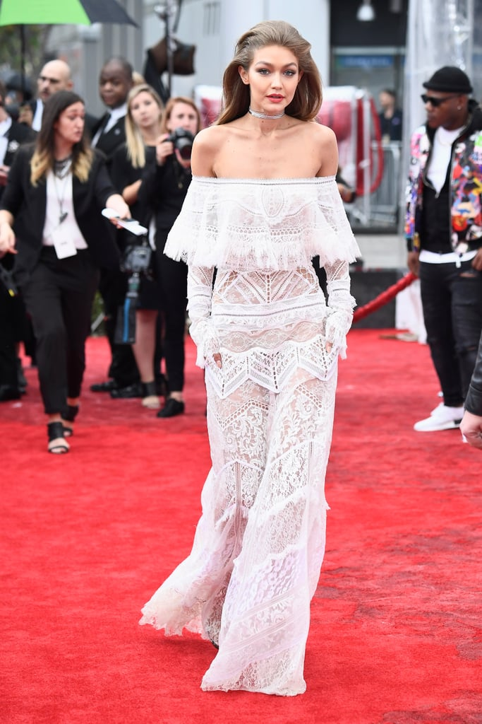Gigi Hadid arrived in style for the American Music Awards in LA on Sunday. The model braved the rain as she hit the red carpet in a white lace Cavalli jumpsuit and looked as gorgeous as usual as she posed for pictures. Gigi is hosting the ceremony along with former SNL star Jay Pharoah, and with performances from Lady Gaga, Bruno Mars, and Nicki Minaj, it should a night to remember. See photos from Gigi's night.