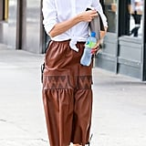 Olivia paired her vintage leather midi skirt with a waist-enhancing, cinched button-down.