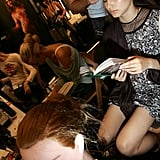 A model used her hair time to catch up on her reading backstage at the Willow Spring 2006 fashion show during Olympus Fashion Week.