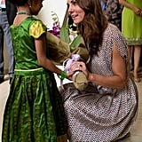 Kate Middleton knelt down to accept flowers from a little girl in a princess costume during a September 2012 stop in Singapore.