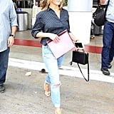 Jen comes off a flight looking casual-cool and effortless in her distressed pair of jeans with strappy espadrille wedges, a Mark Cross bag, and a breezy polka-dot blouse at LAX in June 2017.