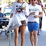 If you've been studying Alessandra's style, you know that she's not afraid of bright colors or bold prints. She did a little bit of both in this outfit, wearing printed cutoffs, a graphic sweatshirt, and baseball cap.