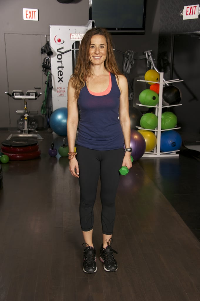 To add a little intensity to this move, stand up straight with your feet together. Hold the weight in your right hand.