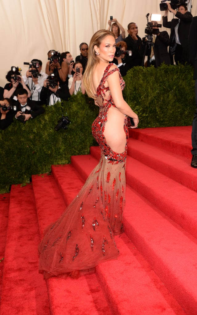 Jennifer Lopez looked hot, hot, hot at the Met Gala in NYC on Monday, flaunting her gorgeous figure in a stunning sequined Versace dress with sheer cutouts. The sexy star posed for pictures on the red carpet, showing off her striking look from every angle. Jennifer was among many famous faces at this year's Met Gala, including Elizabeth Banks, who had a Jennifer Lopez moment of her own in a sleek turquoise dress. Keep reading for the best pictures of J Lo at the Met Gala, then go behind the scenes with the night's most glamorous social snaps!