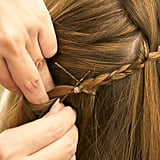 To hide the braided end, tuck it under the layers in the back of your head. Pin it in place by crossing two bobby pins in an X shape.