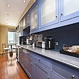 The kitchen is outfitted with hardwood floors and blue cabinets.