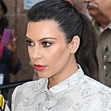 A swept-up ponytail with loads of volume played up Kim's bronze shadow and red lips when she stepped out in Los Angeles this past April.