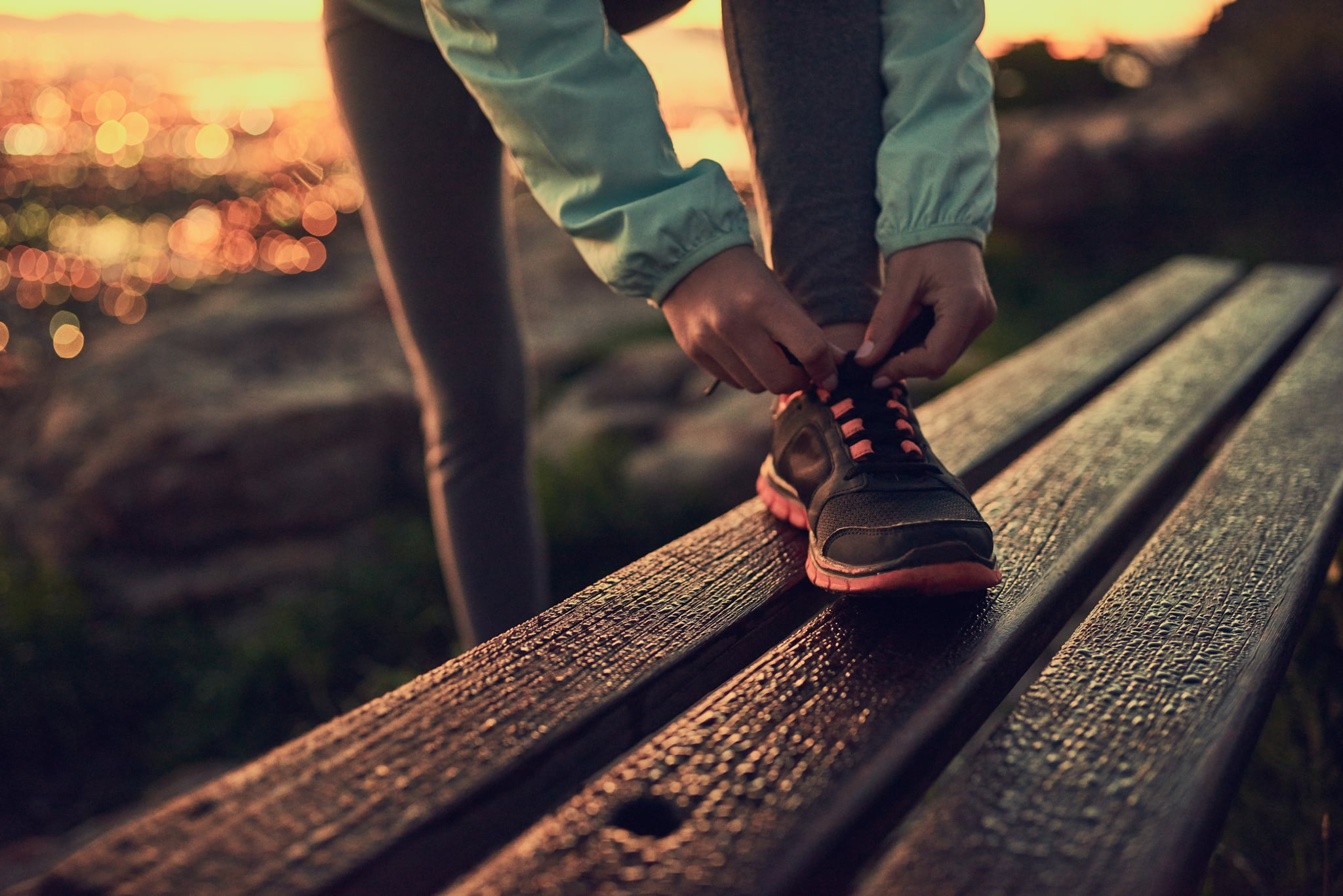 Shot of an unrecognizable woman tying her shoe laces before a run