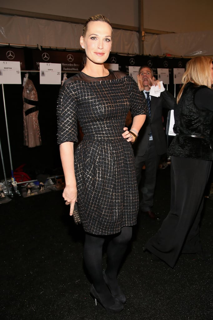 Molly Sims worked a gold-and-black woven dress at Carolina Herrera. Note the unfinished hems and sheer-shoulder detail.