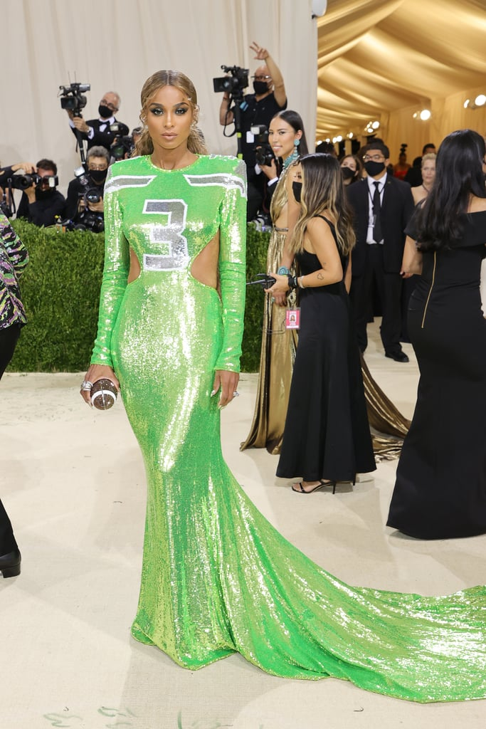 """When it came to the 2021 Met Gala, Ciara understood the assignment and she ran with it . . . she ran with it right into the end zone. On Monday night, the stunning singer and mom of three stepped out on the red carpet wearing a jersey dress by designer Peter Dundas that resembled none other than her husband Russell Wilson's NFL jersey. The lime-green sequined dress was inspired by the Seattle Seahawks quarterback's number 3 jersey. With the theme of the Met Gala being """"In America: A Lexicon of Fashion,"""" Ciara rocked a football-shaped purse and Russell's 2013 Super Bowl ring — because there is nothing more American than football! During her red carpet interview with Keke Palmer for Vogue, Ciara said she and Peter were inspired by Geoffrey Beene's iconic football jersey dresses from the late 1960s. Her dress featured a gorgeous open back and cutouts, and she styled it with a bronde power ponytail. Check out Ciara's Met Gala jersey dress from all angles ahead.      Related:                                                                                                           Every Look From the 2021 Met Gala Red Carpet That We Can't Stop Talking About"""