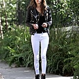 Alessandra Ambrosio kept her color palette black and white in Hudson tuxedo jeans, a black leather biker jacket, Christian Louboutin buckle booties, and Westward Leaning sunglasses during a stroll in LA.
