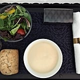 """Soon after you take off, the flight attendants come by to take your order for your three-course meal. I chose the cauliflower cream soup as my first course, which came with a salad and bread. Prepared by """"top Dutch chefs"""", it was actually really delicious. The salad was a perfect touch, considering some airlines offer more greasy foods for long flight."""